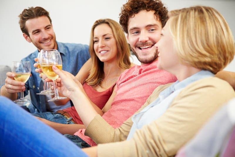 Groep Vrienden die van Glas Wijn thuis genieten stock afbeeldingen