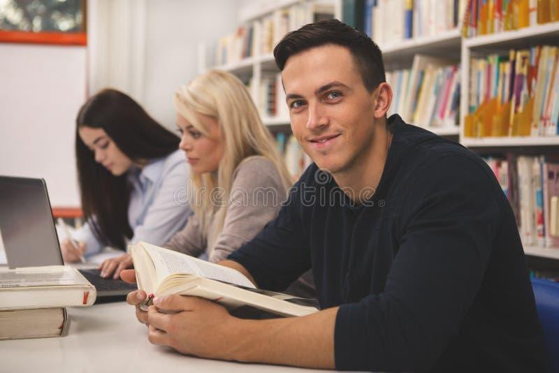 Groep vrienden die van het bestuderen genieten samen bij de bibliotheek stock fotografie