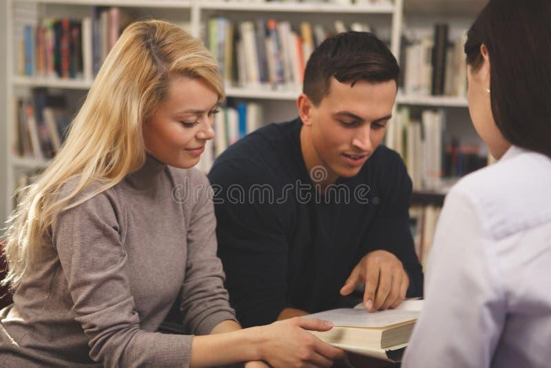 Groep vrienden die van het bestuderen genieten samen bij de bibliotheek royalty-vrije stock foto
