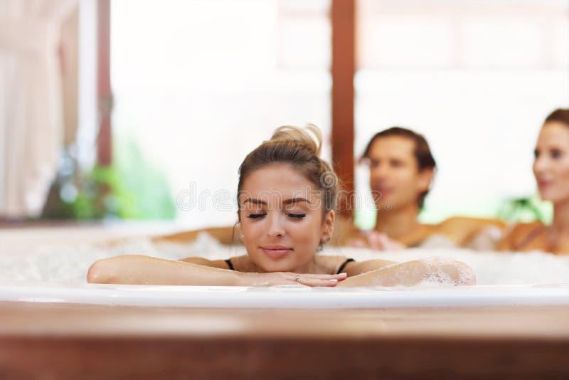 Groep vrienden die van Jacuzzi in hotel spa genieten stock afbeelding