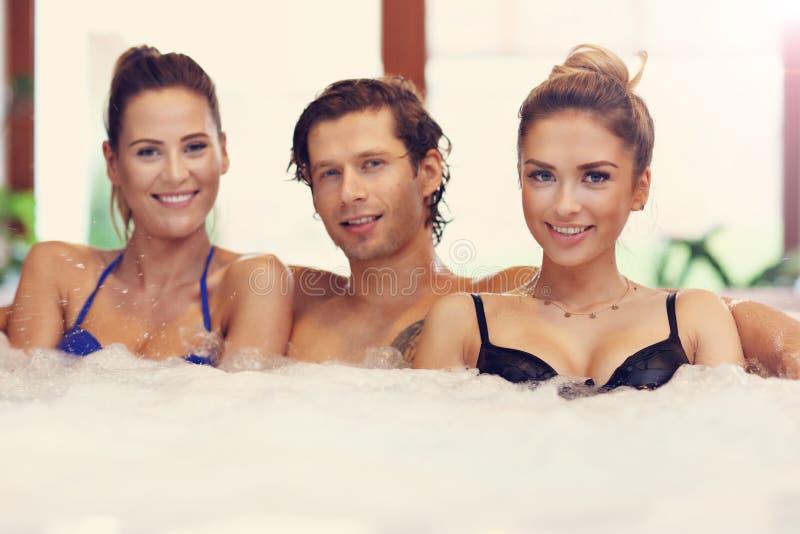 Groep vrienden die van Jacuzzi in hotel spa genieten stock afbeeldingen