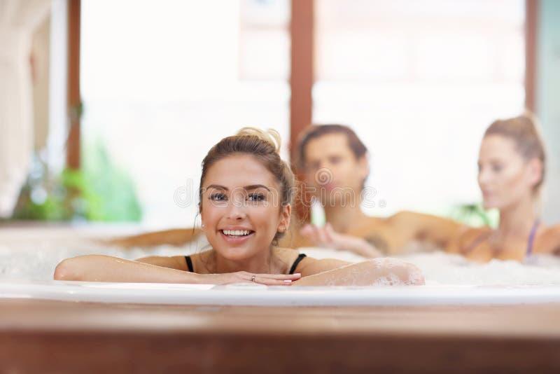Groep vrienden die van Jacuzzi in hotel spa genieten stock fotografie