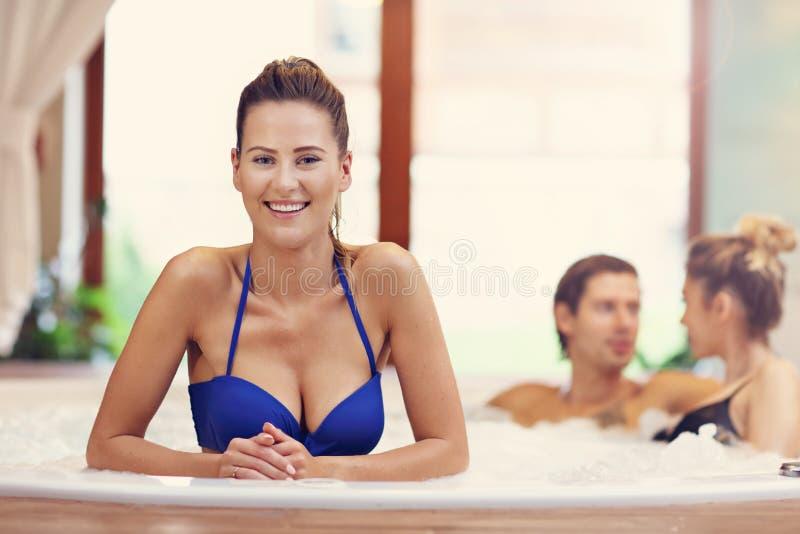Groep vrienden die van Jacuzzi in hotel spa genieten stock foto's