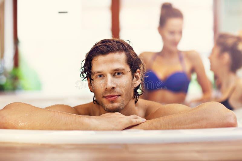 Groep vrienden die van Jacuzzi in hotel spa genieten stock foto