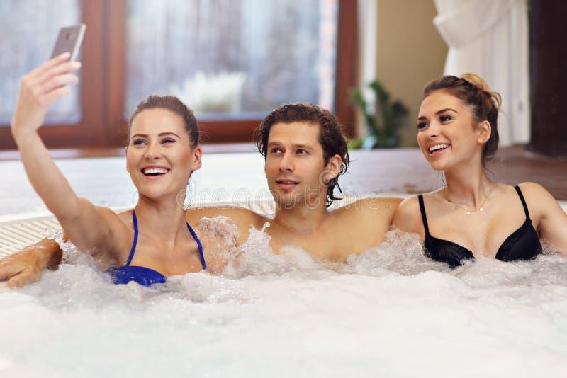 Groep vrienden die van Jacuzzi in hotel spa genieten royalty-vrije stock foto