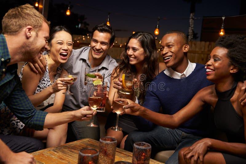 Groep Vrienden die van Nacht genieten uit bij Dakbar royalty-vrije stock foto's