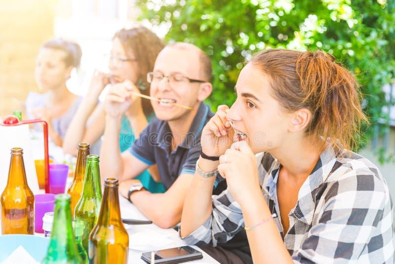 Groep vrienden die vleesvleespennen eten royalty-vrije stock afbeelding