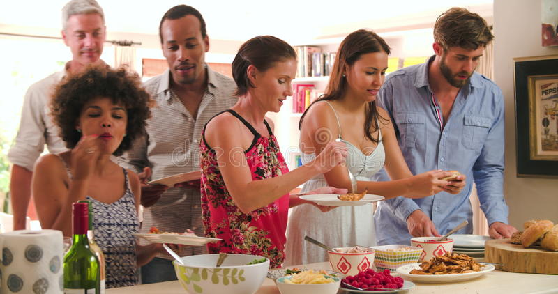 Groep Vrienden die Voedsel thuis kiezen van Partijbuffet