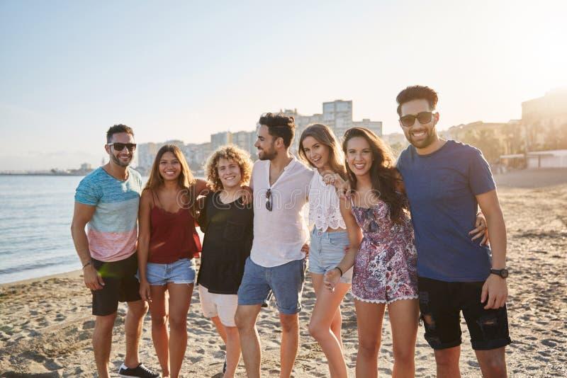 Groep vrienden die zich bij strand het glimlachen verenigen royalty-vrije stock afbeelding