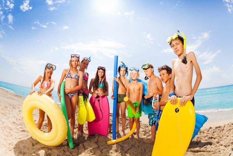 Groep vrienden die zich op het zonnige strand bevinden stock afbeeldingen