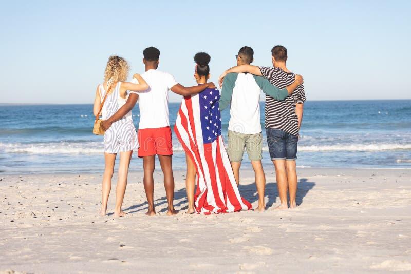 Groep vrienden die zich samen met Amerikaanse vlag op het strand bevinden stock afbeeldingen