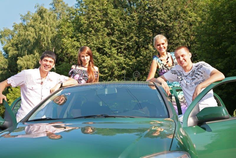 Groep vrienden met auto openlucht royalty-vrije stock fotografie