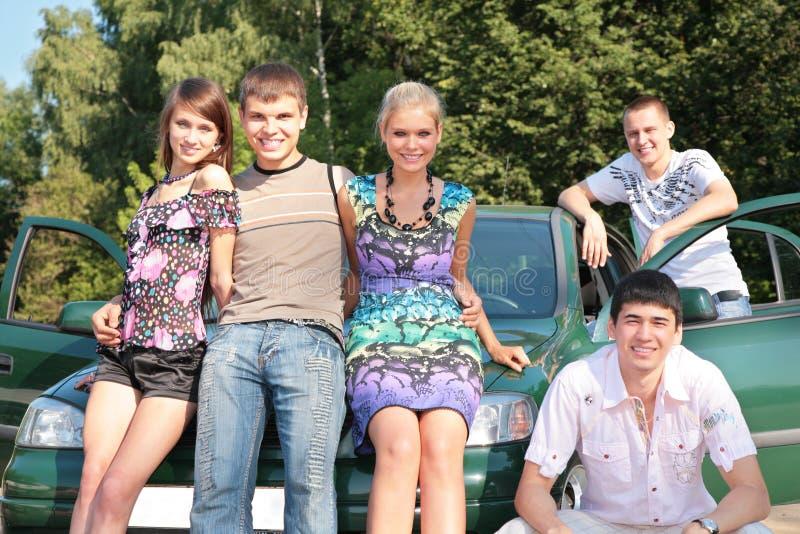 Groep vrienden met auto openlucht stock fotografie