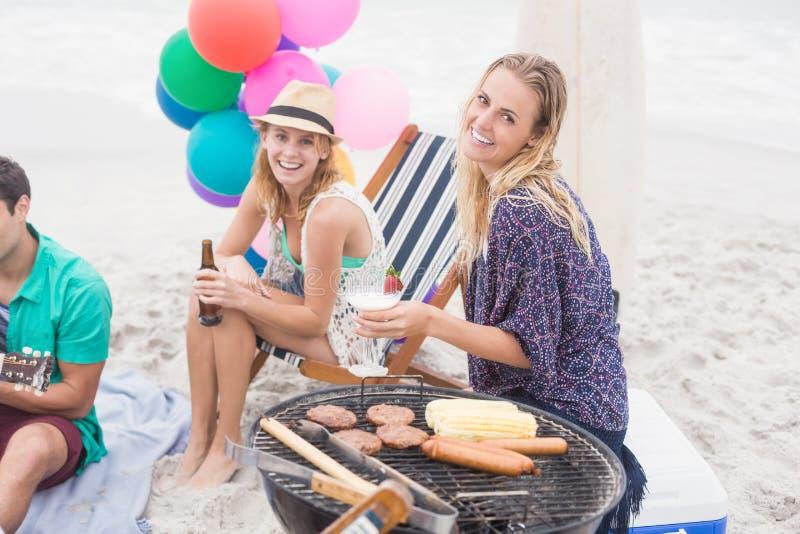 Groep vrienden met dranken die naast een barbecue zitten stock afbeelding