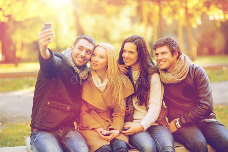 Groep vrienden met fotocamera in de herfstpark stock afbeeldingen