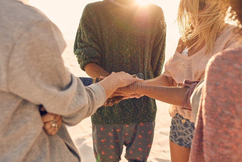 Groep vrienden met handen op stapel bij kust stock afbeeldingen
