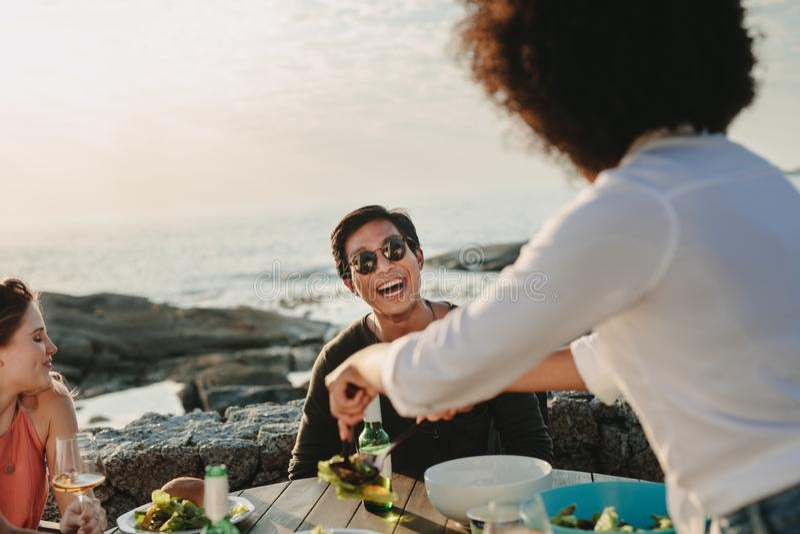 Groep vrienden op een vakantie die van voedsel en dranken genieten bij B stock afbeeldingen