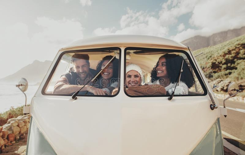 Groep vrienden op roadtripzitting binnen minivan stock fotografie