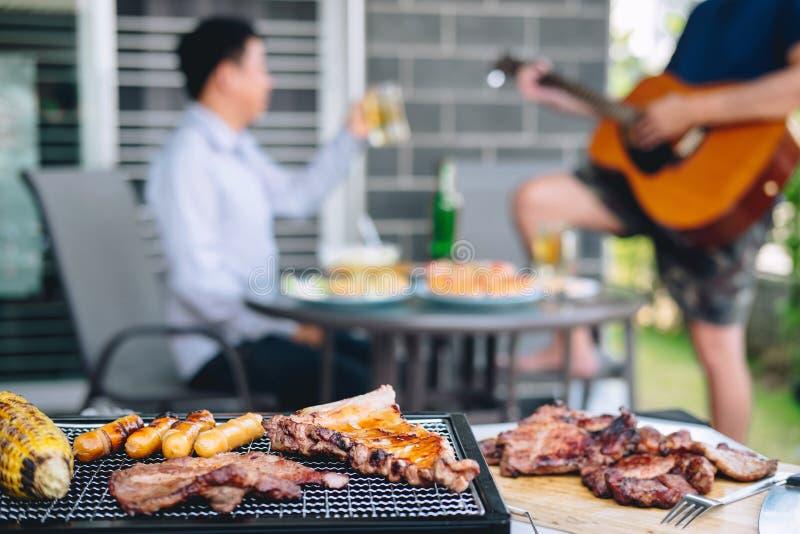 Groep vrienden Twee jonge mens die van geroosterde vlees en spelgitaar met verhoging genieten een glas bier om het vakantiefestiv royalty-vrije stock afbeeldingen