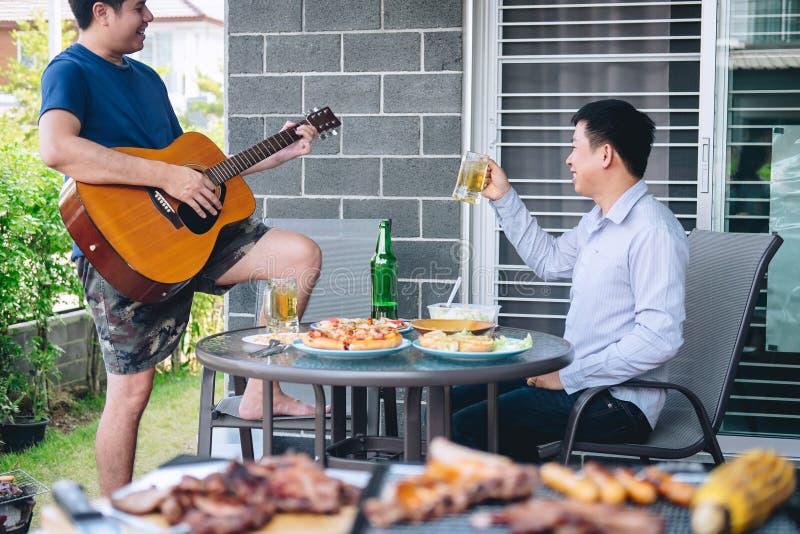 Groep vrienden Twee jonge mens die van geroosterde vlees en spelgitaar met verhoging genieten een glas bier om het vakantiefestiv royalty-vrije stock fotografie