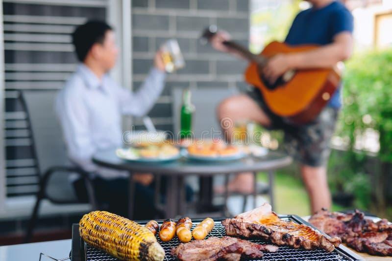 Groep vrienden Twee jonge mens die van geroosterde vlees en spelgitaar met verhoging genieten een glas bier om het vakantiefestiv royalty-vrije stock afbeelding