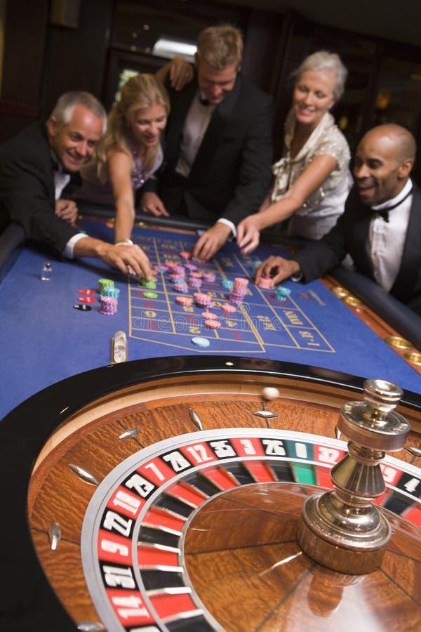 Groep vrienden van het gokken in casino royalty-vrije stock afbeeldingen