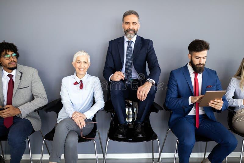 Groep vriendschappelijk zakenlui met mannelijke leider vooraan royalty-vrije stock afbeeldingen