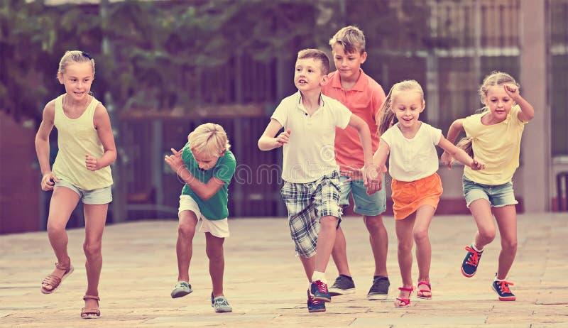 Groep vriendschappelijke kinderen die samen in stad op de zomer lopen stock afbeelding