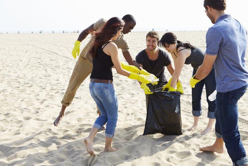 Groep Vrijwilligers die Vuilnis op Strand opruimen stock foto