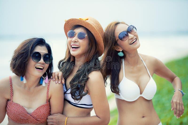 Groep vrolijke Aziatische jongere vrouw die strandbikini dragen die met gelukemotie lachen stock foto