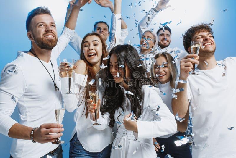 Groep vrolijke blije jongeren die en zich over blauwe achtergrond verenigen vieren royalty-vrije stock foto's