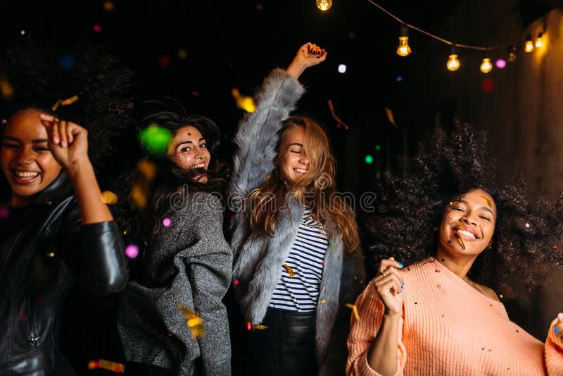 Groep vrouwelijke vrienden die bij nacht dansen stock foto's