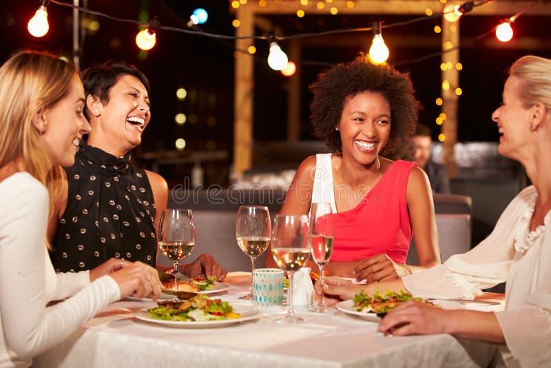 Groep vrouwelijke vrienden die diner eten bij dakrestaurant stock foto's