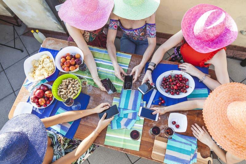 Groep vrouwelijke vrienden die kleurrijke hoeden dragen die pretverslaving hebben aan smartphone stock fotografie