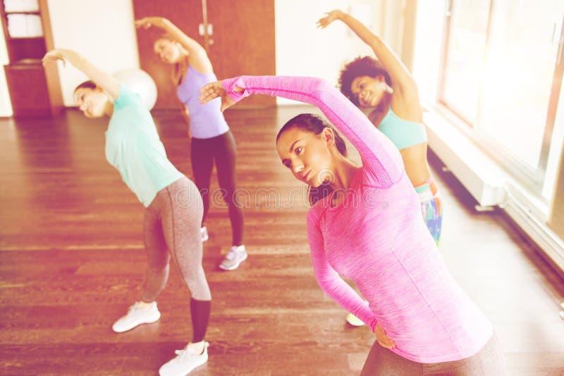 Groep vrouwen die en zich in gymnastiek uitoefenen uitrekken stock fotografie