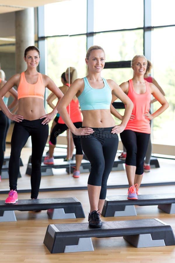 Groep vrouwen die met steppers in gymnastiek uitwerken royalty-vrije stock afbeeldingen