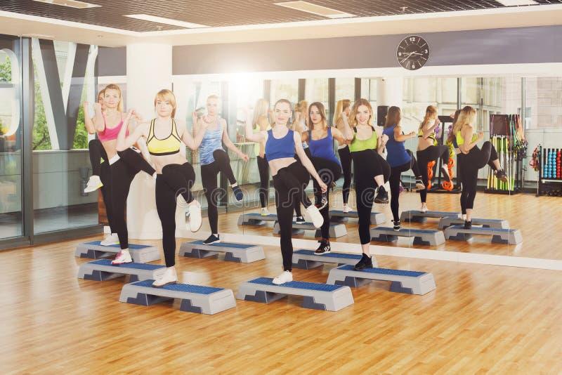 Groep vrouwen, stapaerobics in geschiktheidscentrum stock foto's
