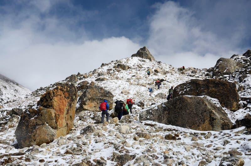 Groep wandelaars die bergketen, Everest-Basiskamp beklimmen stock afbeeldingen