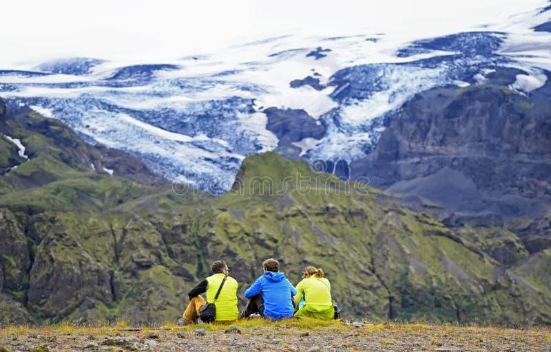 Groep wandelaars die op een richel die van een berg zitten, van de mooie meningsvallei in Thorsmork genieten stock fotografie