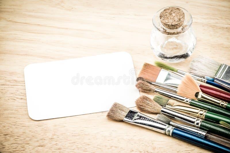 Groep waterverfborstel en lege Witboekkaart op houten lusje royalty-vrije stock fotografie