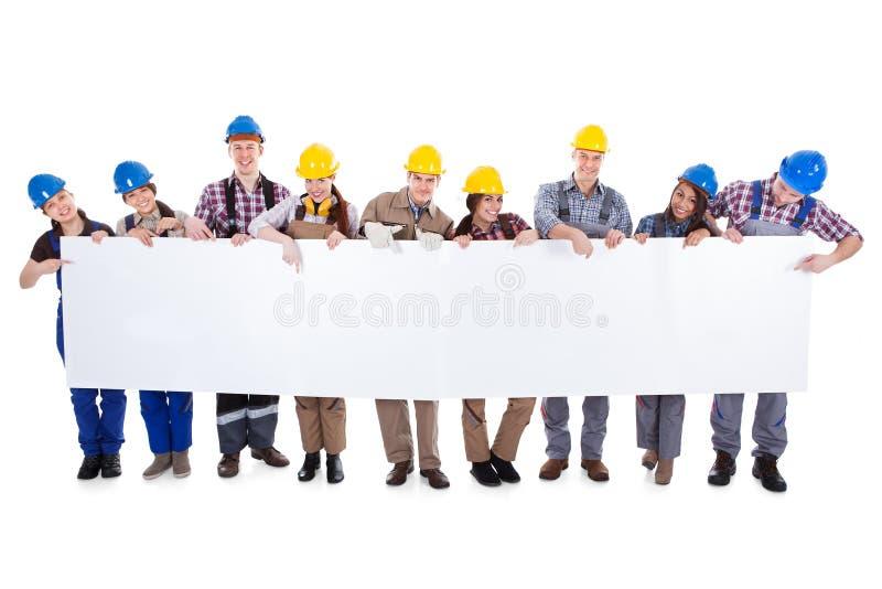 Groep werklieden en vrouwen met een banner stock foto