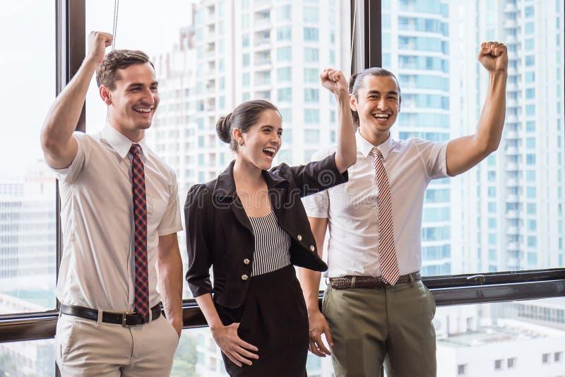Groep werknemers met hun handen die en pret in de commerciële vergadering samenhouden hebben stock foto
