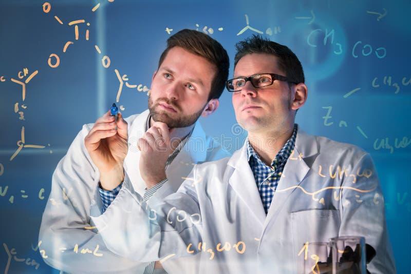 Groep wetenschappers die bij media het scherm werken stock fotografie