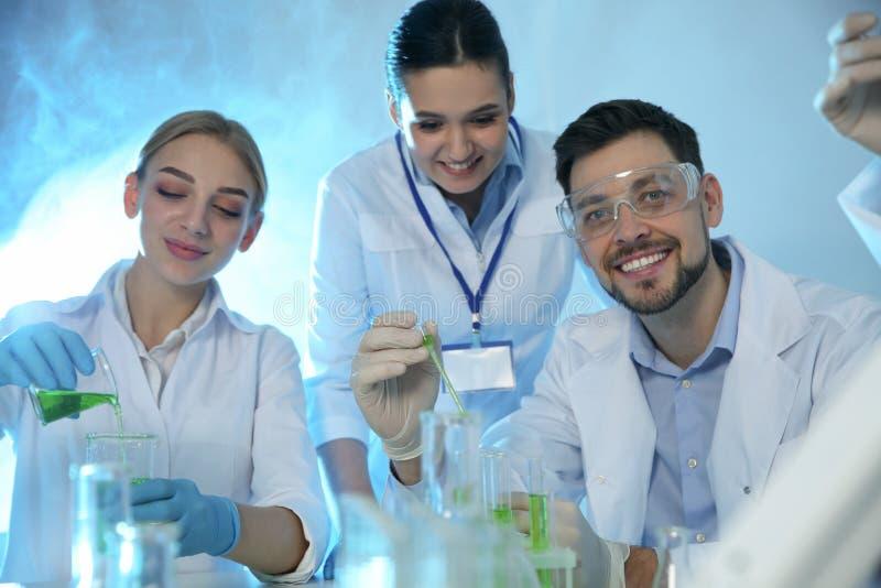 Groep wetenschappers die in chemielaboratorium werken stock foto's