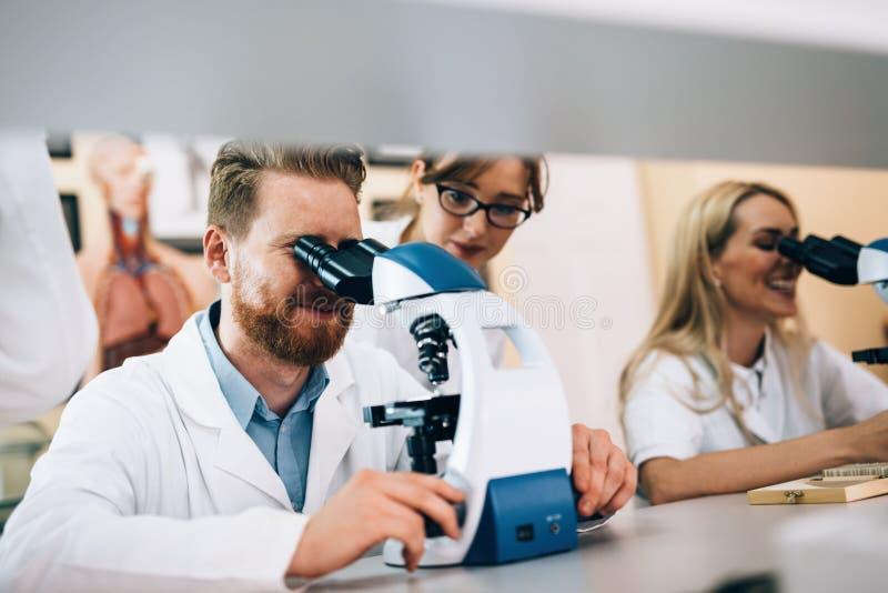 Groep wetenschappers die onderzoek doen die door microscoop kijken stock afbeeldingen