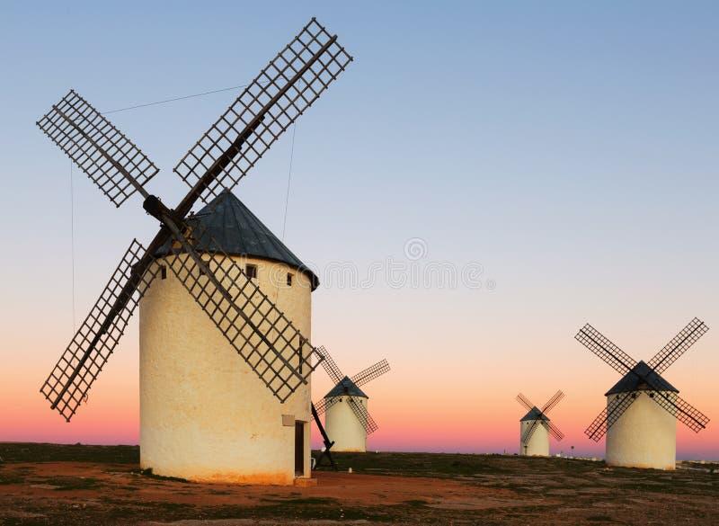 Groep windmolens bij gebied in zonsopgang stock foto's