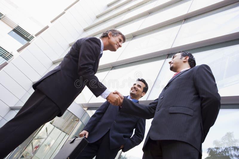 Groep zakenlieden die handen buiten bureau schudden royalty-vrije stock fotografie