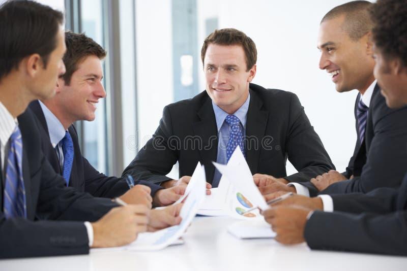 Groep Zakenlieden die Vergadering in Bureau hebben stock afbeelding