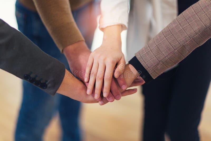 Groep zakenlui die hun handen bovenop elkaar zetten royalty-vrije stock afbeelding