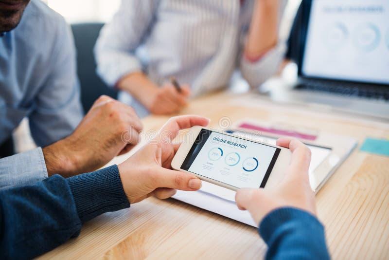 Groep zakenlui met smartphone die in bureau, midsection samenwerken stock foto